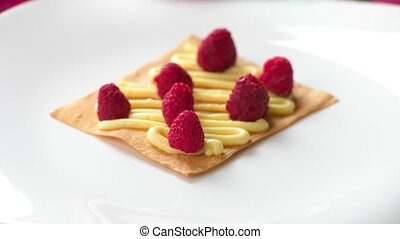 Hand puts shortcake on raspberries Cream and berries on...