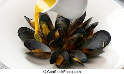 Jug pours sauce on mussels. Cooked mussels on white...