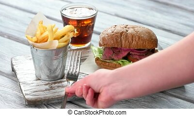 Hand puts knife and fork Cutlery beside french fries Fresh...