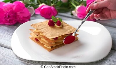 Spoon smears sauce on plate. White plate with raspberry...