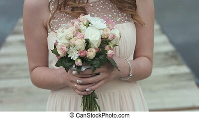 Bride hold the wedding bouquet in her hands