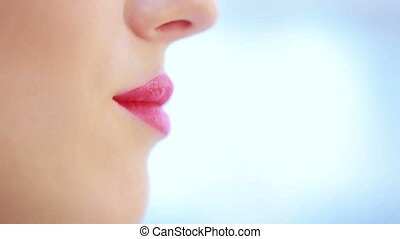 close up of young woman lips over blue. color lipstick