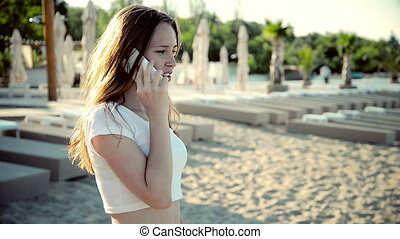 Young Girl Talking at Mobile Phone Beach in Summer Holidays.