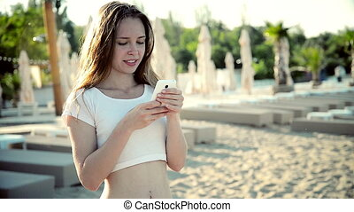 Woman using smartphone with earphones laughing on beach...