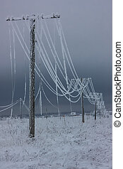 Broken phase electrical power lines with hoarfrost on the wooden electric poles on countryside in the winter