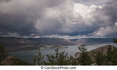 Stormy clouds above a big lake - Moving stormy clouds above...