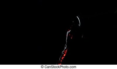 Pouring red wine from green bottle, dark background, super...