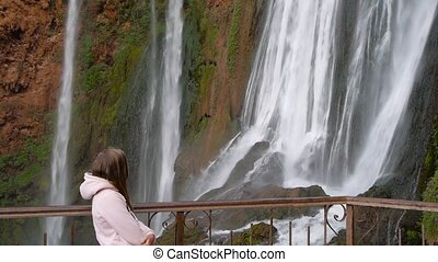 woman traveler in bright clothes resting by the Ouzoud waterfall in Morocco