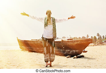 Girl on the old fishing boat Rajbag beach of South Goa,...