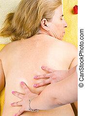 Mature woman getting back massage at spa salon