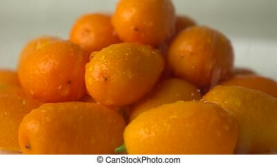 Small water drops hit heap of orange kumquat. Super slow...