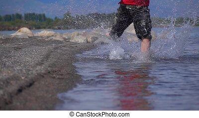 Super slow motion shot of unknown man running on shallow...