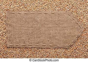 Pointer of burlap lying on a wheat background