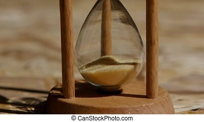 Bottom portion of an hourglass with yellow sand. Close up -...