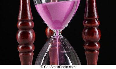Sand falls quickly through an hourglass. Black. Close up -...