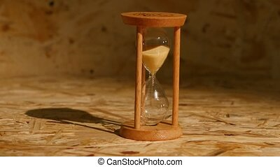 Sand falls quickly through an hourglass, lot of sand grains,...