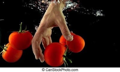 Man hand reaches and grabs tomato floating under water super slow motion shot