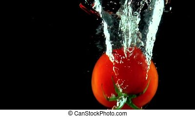 Single red ripe tomato with green leaves falls under water super slow motion