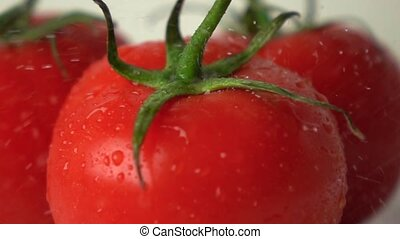 Small water drops hit red ripe tomato with green leaves...