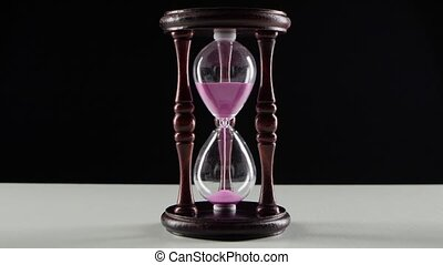 Wooden hourglass. Jet of sand in the hourglass. Black -...