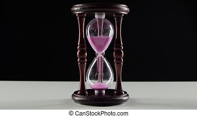 Countdown in the hourglass Pink sand Black - Pink sand pours...