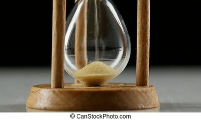 Bottom portion of an hourglass with a sand. Black. Close up