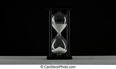 Black hourglass. White sand. Black