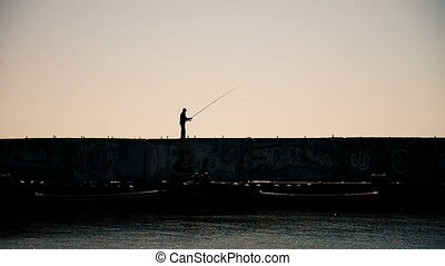A man fishing from the breakwaters wall with industrial...