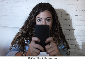 hispanic woman holding mobile phone in crazy eyes social...