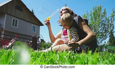 Mother and daughter playing on the lawn