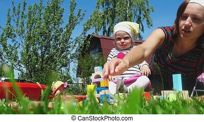 Mother and daughter playing on the lawn - Young mother plays...