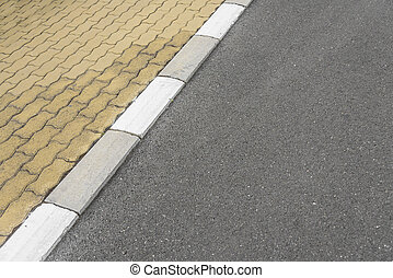 Border sidewalk and the asphalt road. - Striped border...