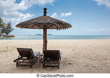 Two lounge chairs and a sunshade umbrella on the beach - Two...
