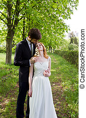 Couple bride and groom walking in the park showing the most...
