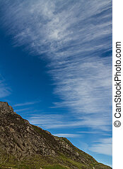 Cirrus cloud above mountain and in blue sky