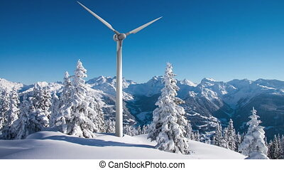 Rotating wind turbine above sunny snowy forest in the...