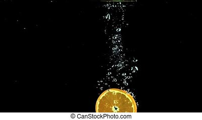 Orange slice falls into water against black background super slow motion video
