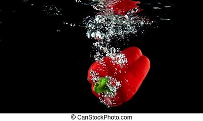 Whole red ripe sweet pepper falls into water super slow motion video
