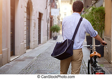 Photo of a man walking with his bike in city