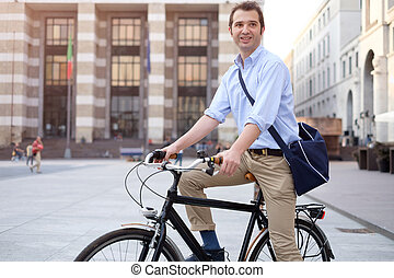 Photo of a handsome smiling man riding bike in city -...