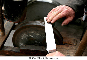 Grinder with hands sharpen a blade of a knife - Elder...