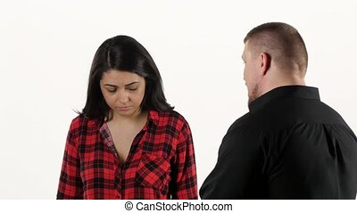 Annoyed man yelling at frightened woman on white background...