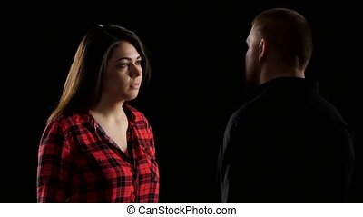 Emotional conversation couples. Woman covers ears and screams. Black. Close up