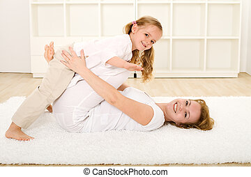 Little girl and woman playing indoors on the floor