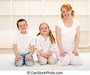 Happy woman and kids indoors sitting on the floor