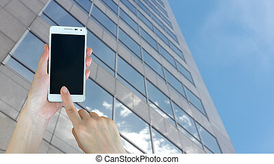 Hand holding blank screen smart phone with buiding background