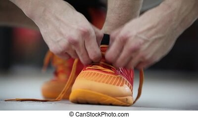 The athlete tying shoelaces on sneakers. Preparation for the...