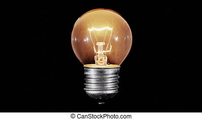 Tungsten light bulb lamp blinking over black background,...