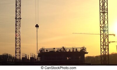 Silhouettes of cranes and construction site workers against...