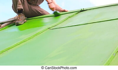 Man Painting Roof With Proceting Layer - Adult caucasian man...